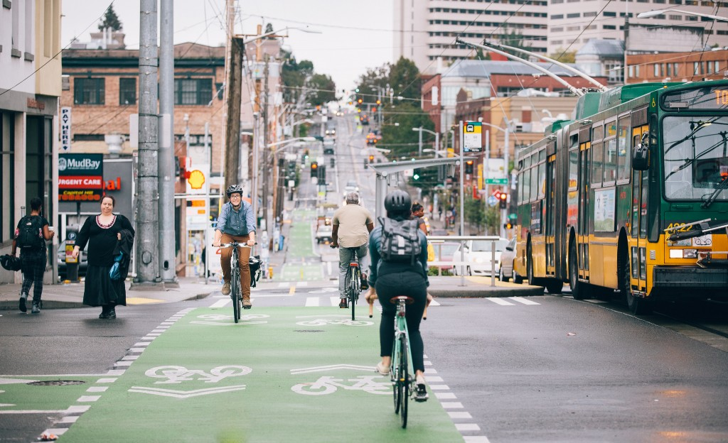 A woman on a bike in a protected lane surrounded by other people on bikes, walking, a bus, and a busy urban street.