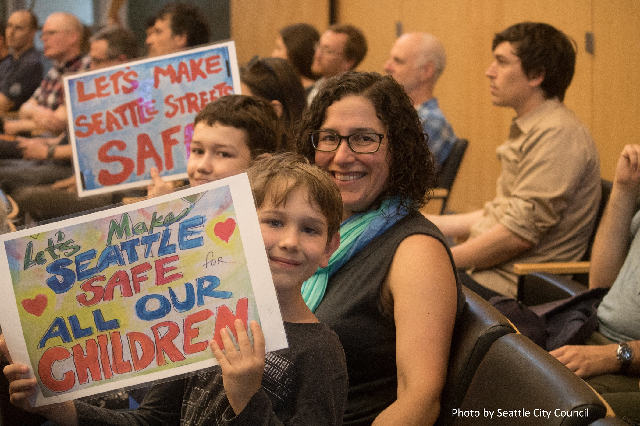 A woman and her two children sit in the City Council chambers smiling and holding handmade signs in support of safe streets.