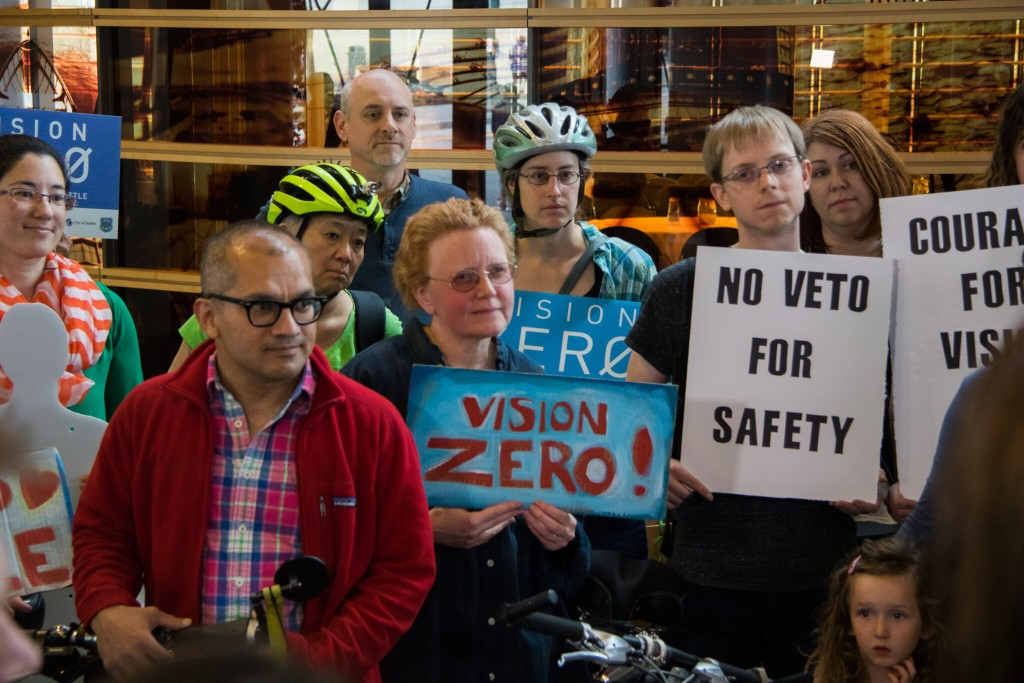 A group of people with helmets and bikes hold signs calling for safety and Vision Zero.