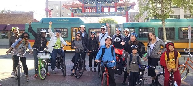 A mixed group of people with bikes stands in front of the Chinatown Arch in Seattle, smiling and waving.