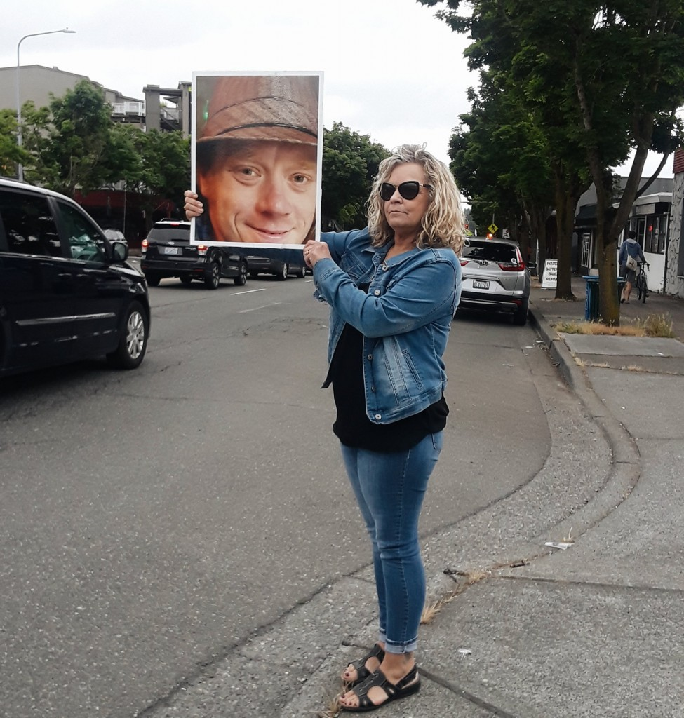 Jesse Gurnett's mother stands on the side of the street holding a photo of her son after he was hit by a car and killed while crossing the street.