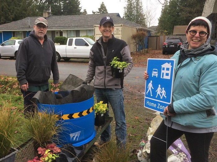 Three people stand smiling while assembling a planter and holding a Home Zone sign.
