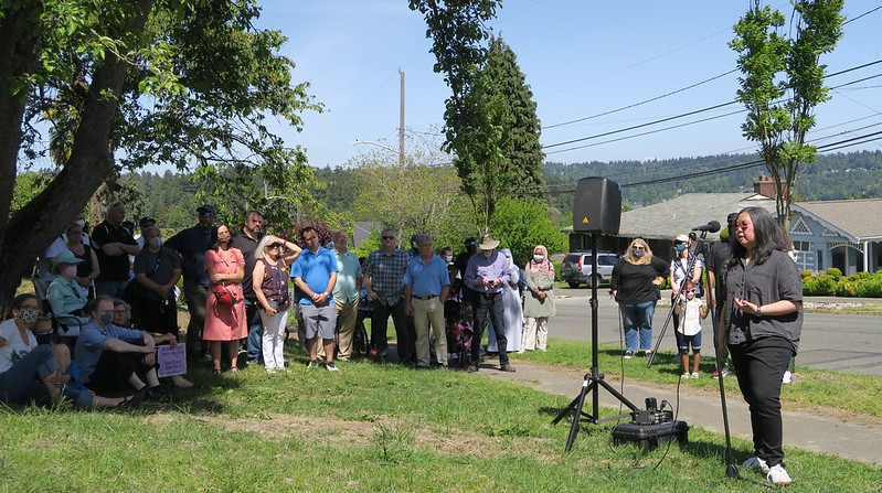 Vanessa Chin speaks into a microphone in a grassy space. A group of people stand and sit somberly behind her.