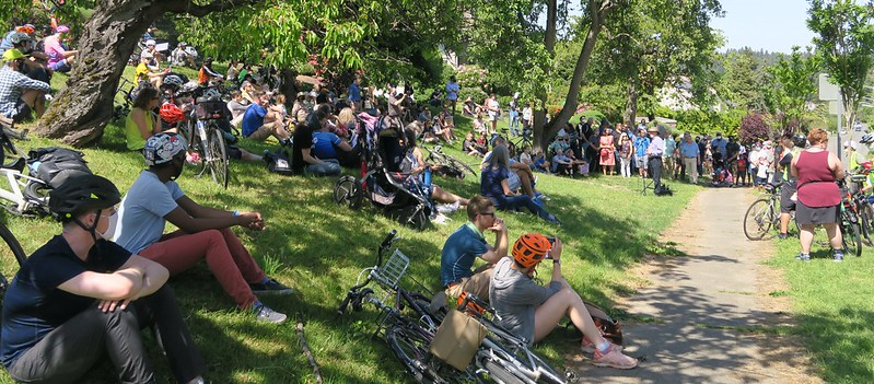 A large crowd of people on a grassy slope. Many wear helmets or sit next to bicycles.