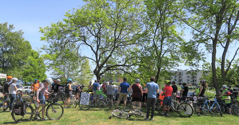 """A crowd of people with bicycles. A bike in the center has a baby seat and a sign that reads """"Safe Streets for the South End."""""""