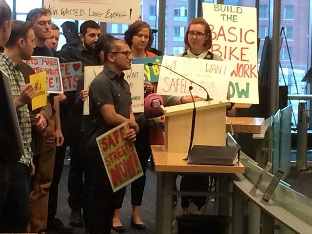 Apu testifying at City Council surrounded by people holding signs in support of the basic bike network.