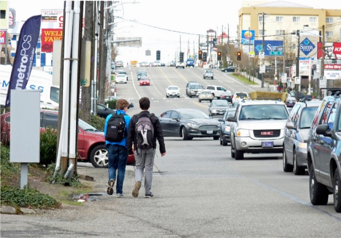 Two people walk beside 7 lanes of traffic on Aurora Ave.