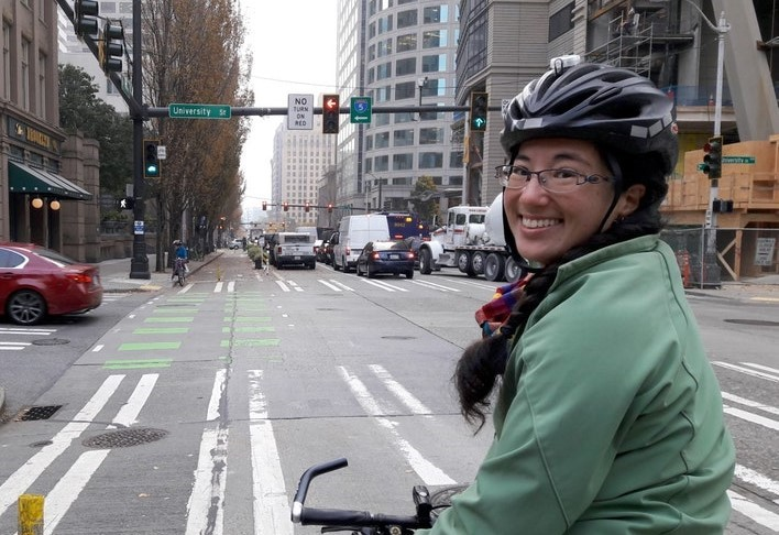 Clara Cantor riding a bike in downtown Seattle.