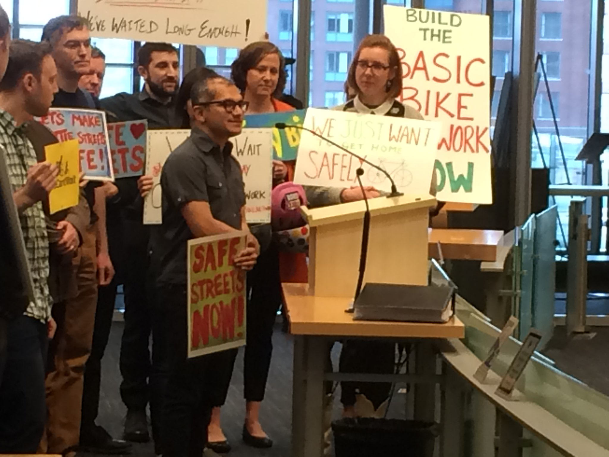 A group of people holding signs in support of the Basic Bike Network gathered around a speaker at a microphone.