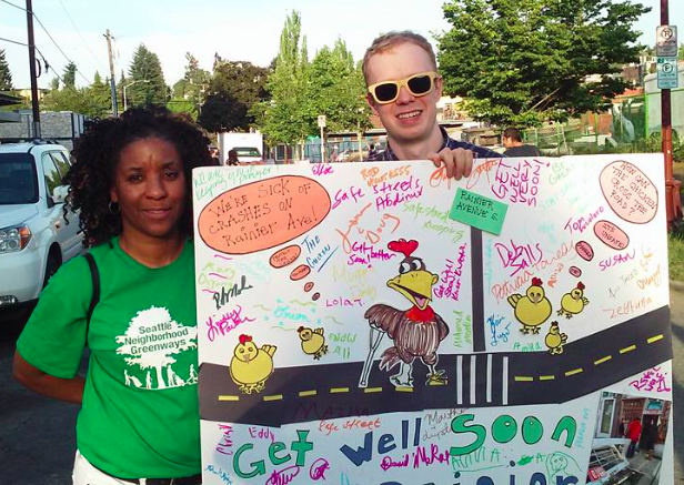 Get Well Card for Businesses Hit By Cars held by SNG staff Phyllis Porter & Gordon Padelford on Rainier Ave S