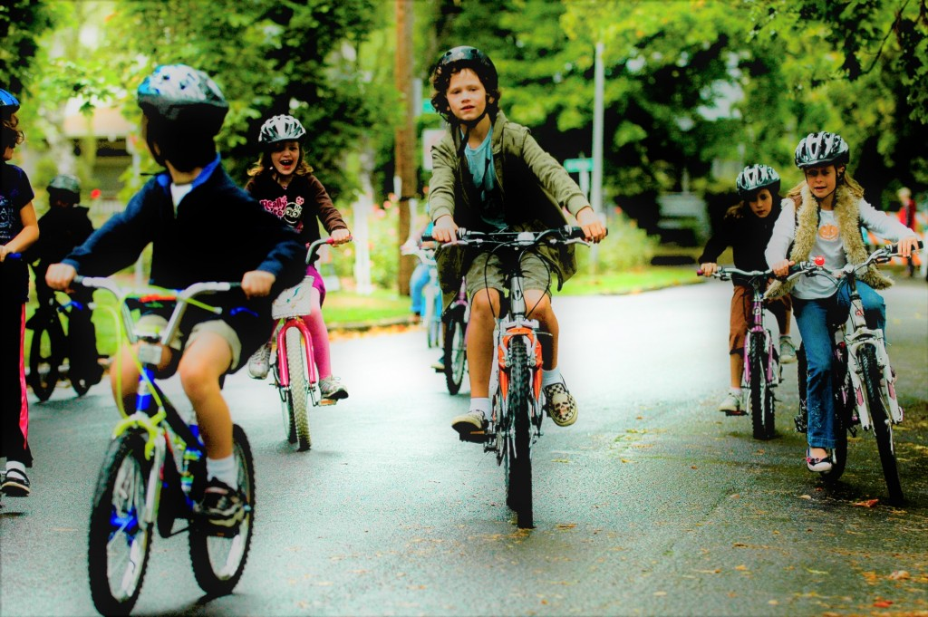 A group of smiling kids riding bicycles down the street.