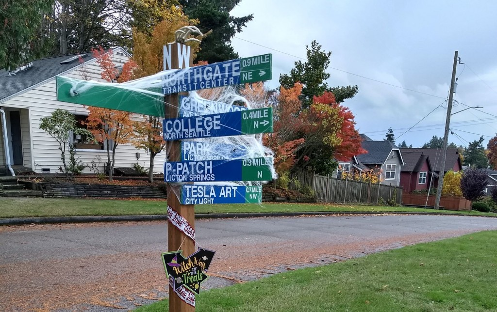 A home-made wayfinding sign with walking times and distances, decorated for Halloween.