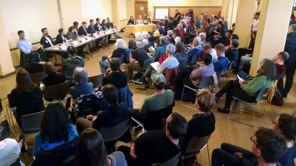 A crowded room of people sitting facing a panel of candidates at the front of the room.