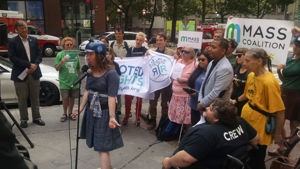 A woman wearing a bike helmet stands at a microphone in front of a crowd of people holding signs, some with mobility aids.