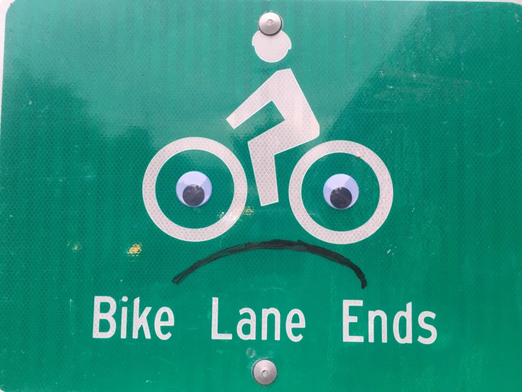 "Official sign reading ""Bike Lane Ends"". Someone has added googly eyes and a frowning face."