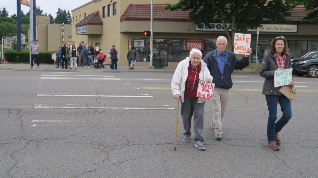 Three pedestrians, one with a mobility aid, cross the street holding signs asking for safe crossings.