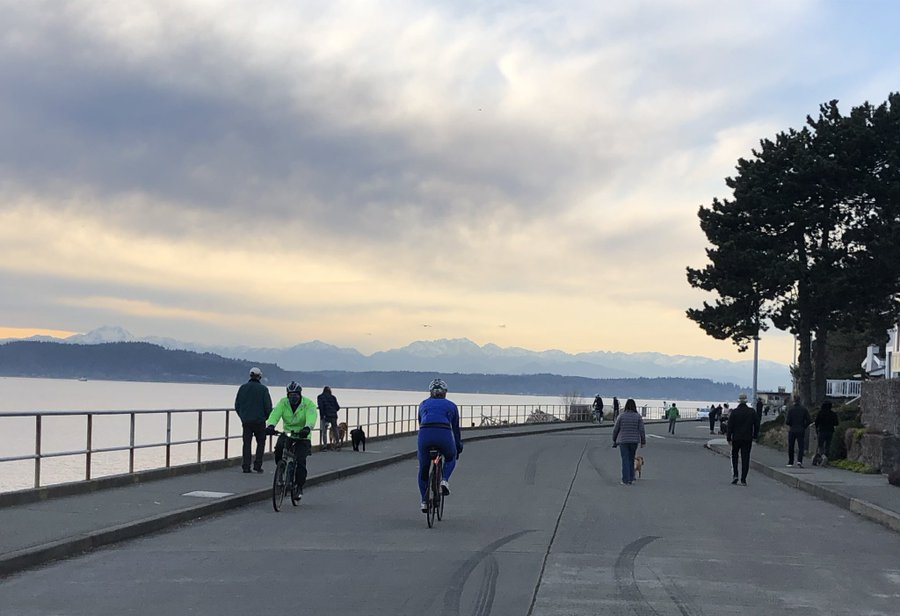 People walking and biking in the middle of the street in front of a beautiful view of water and mountains at dusk..