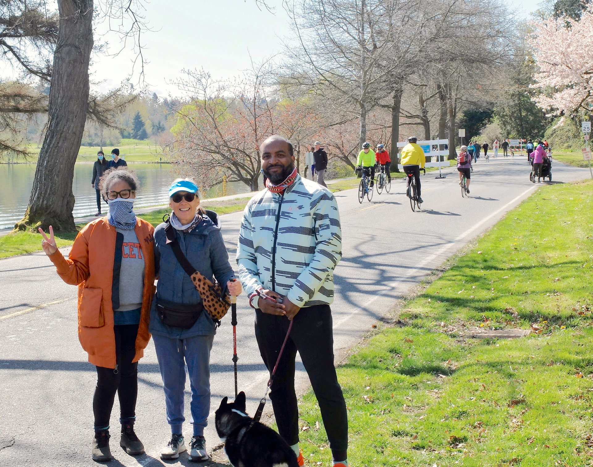 A mixed race family smiles for the camera with their dog in front of a boulevard full of people walking and biking next to a lake.