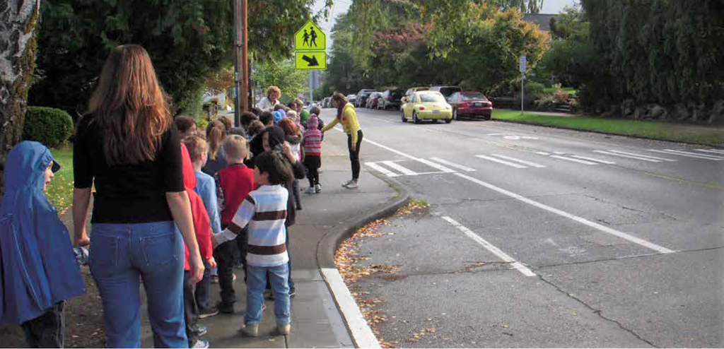 A group of small kids walking with adult supervision wait at a crosswalk.