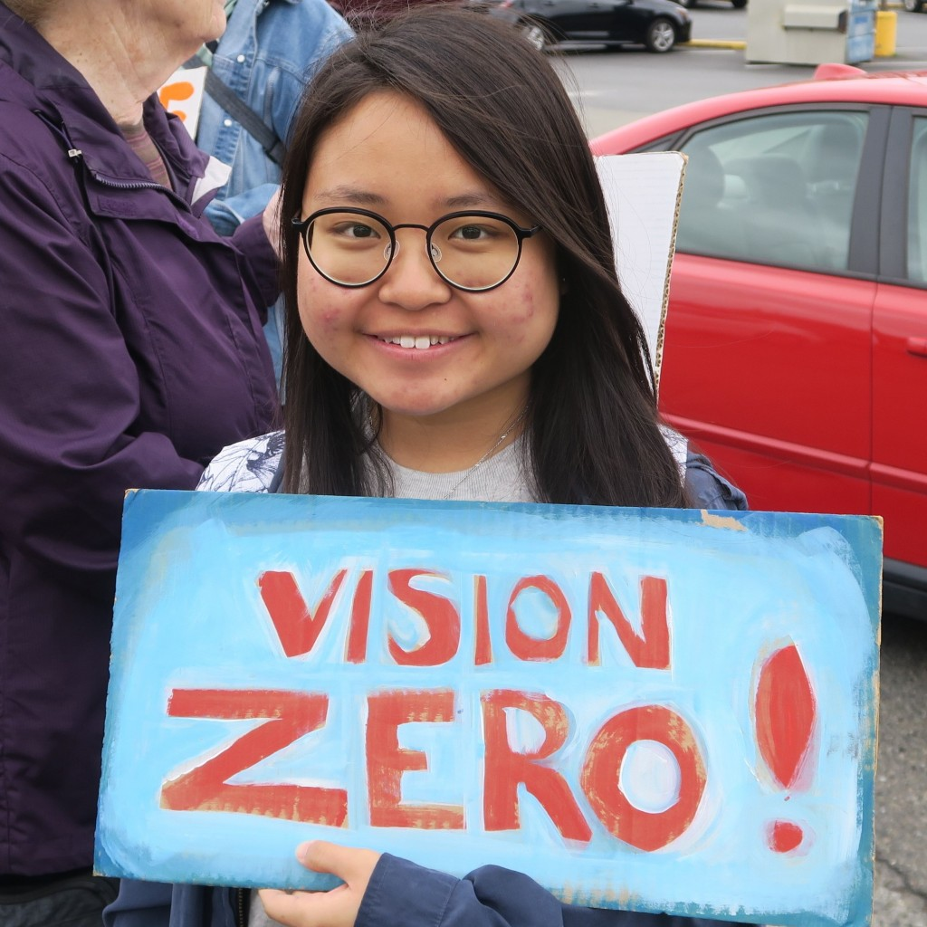 Li Tan holding a sign that reads: Vision Zero!