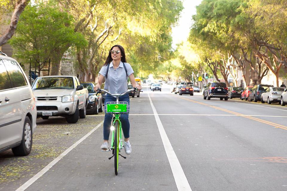 A woman with dark hair rides a lime bike down a tree-lined street.