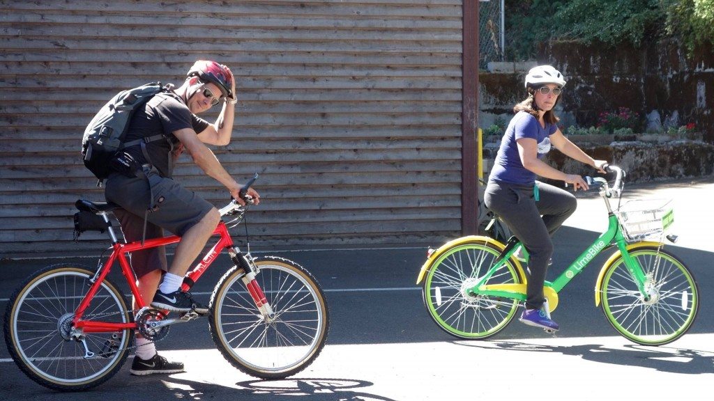 Two people on bikes in front of the Duwamish Longhouse.