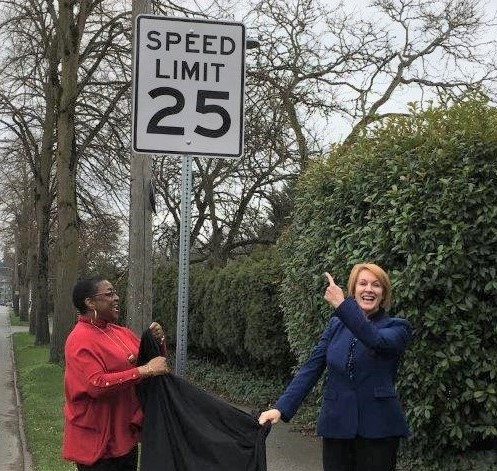 Mayor Durkan and Lynda Greene unveiling a 25 mph speed limit sign.
