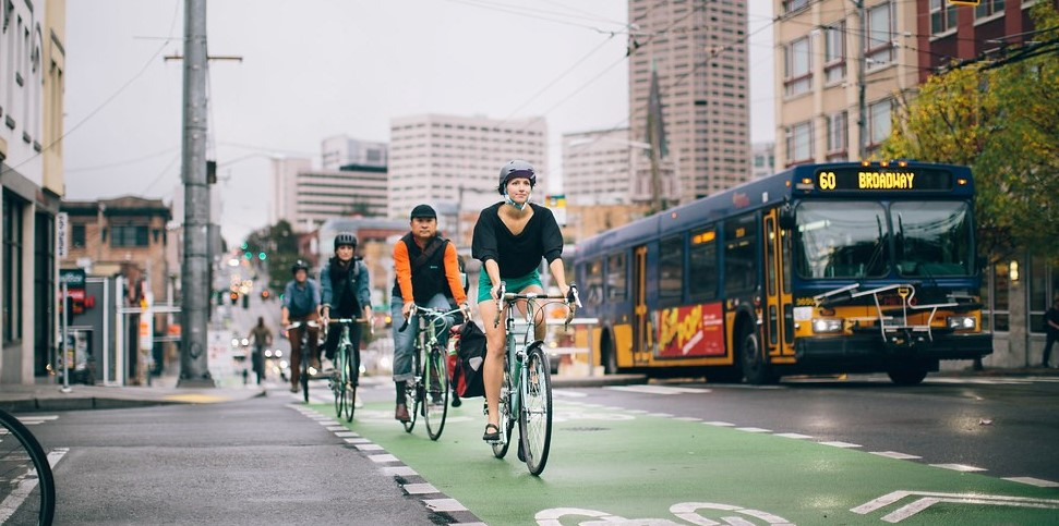 A row of people on bicycles in a protected lane share the street with a King County Metrobus.
