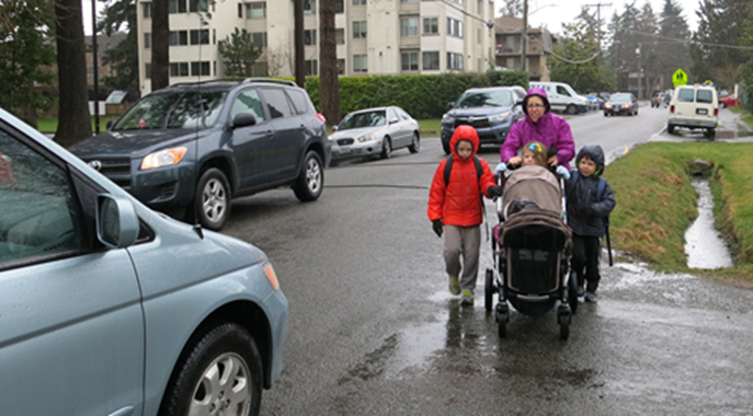 A woman with three kids push a stroller along a street surrounded by cars. There is no sidewalk and they walk between a ditch and moving traffic.