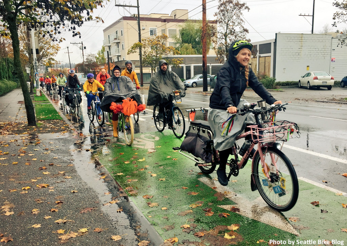 A smiling group of people bike past in a separated bike lane wearing colorful rain coats and ponchos.