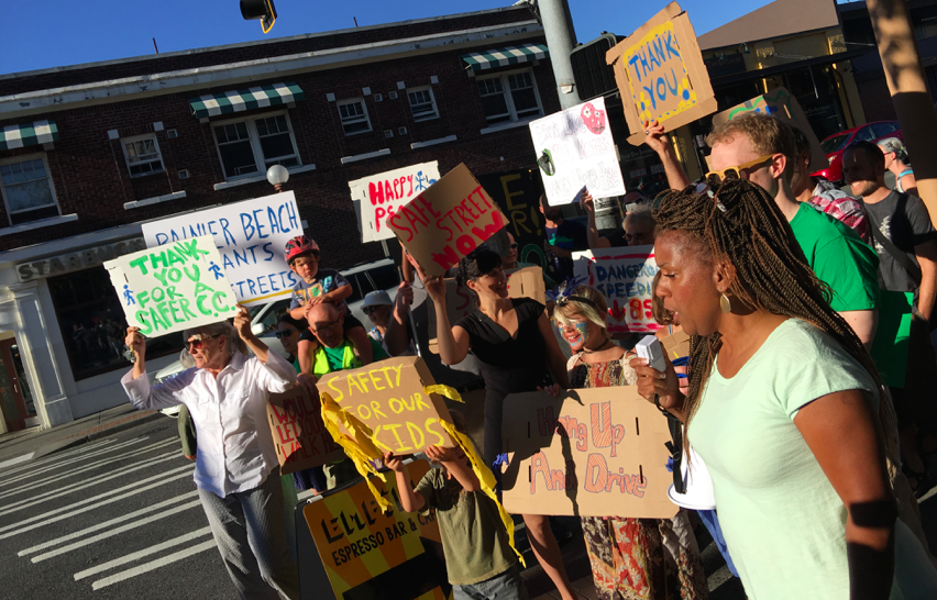 A group of people protesting. A black woman with long hair stands front right with a megaphone. People behind her hold signs in support of Rainier Ave Safety.