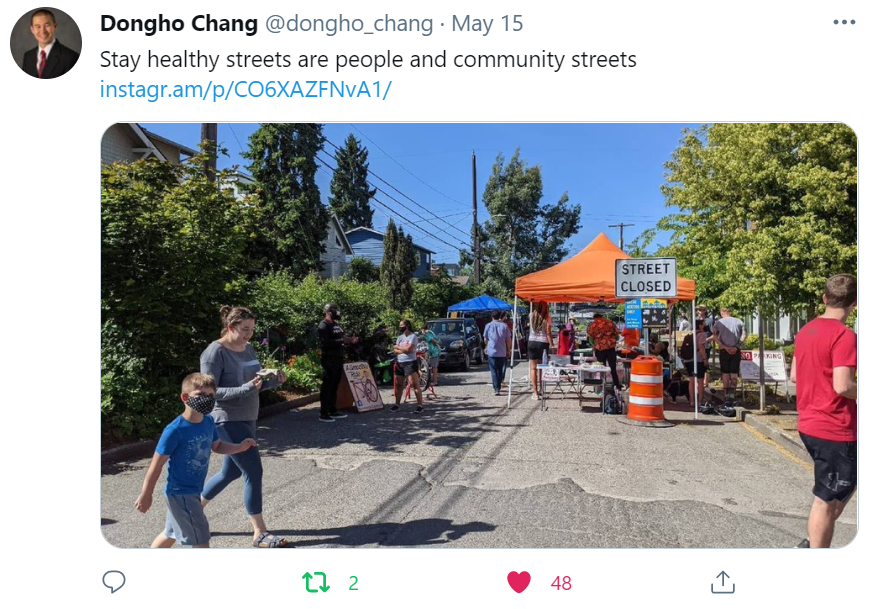 """A tweet by Dongho Chang with a photo of people and tents crowding a street. It reads: Stay Healthy Streets are people and community streets."""""""