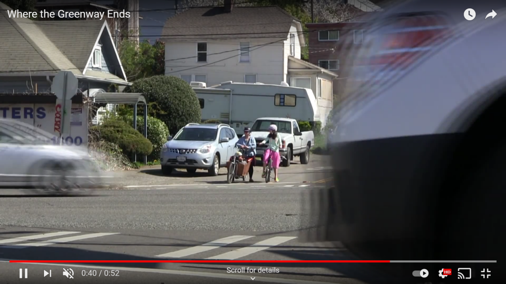 A video still of two women on bikes waiting to cross a busy street.