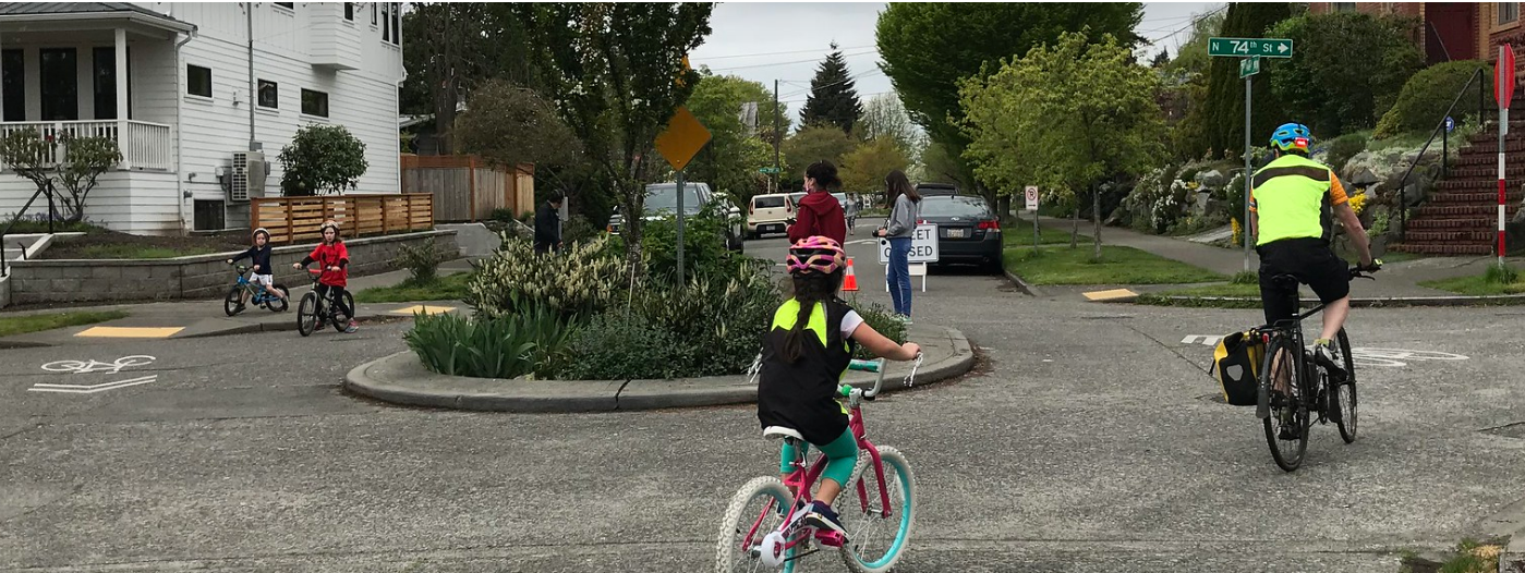 A group of kids on bikes ride around a round-about in front of a
