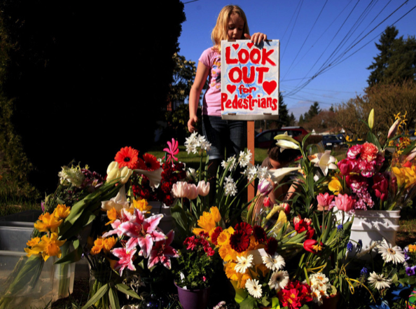 A pile of flowers on the side of the street with a sign that reads: look out for pedestrians.